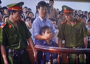"In this photo taken from television shows a security man covers the mouth of the dissident Catholic priest Nguyen Van Ly, 60, after he twice yelled ""Down with the Communist Party"" during his trial for spreading propaganda against the state at a local court in the central city of Hue, 30 March 2007. A Vietnamese court on 30 March sentenced dissident Catholic priest Nguyen Van Ly to eight years in jail for spreading propaganda against the state.    AFP PHOTO/HOANG DINH Nam      VIETNAM OUT NO INTERNET"